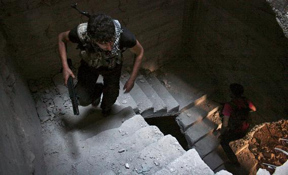 Free Syrian Army fighters run up the stairs of a building in Aleppo's Salaheddine neighborhood.