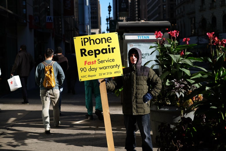 """A man dressed in a winter coat holds a sign that reads """"iPhone Repair Fast Service 90 day warranty"""""""