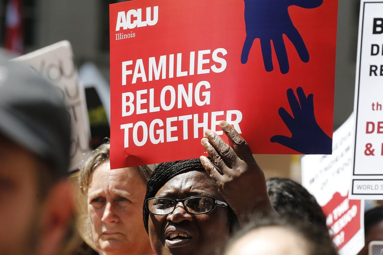"A crowd of protesters, one holding up an ACLU sign that says ""Families Belong Together."""