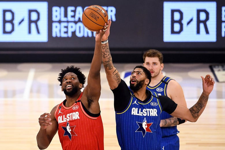 Joel Embiid and Anthony Davis battle for a tip-off during the NBA All-Star Game; Luka Doncic looks on in the background.