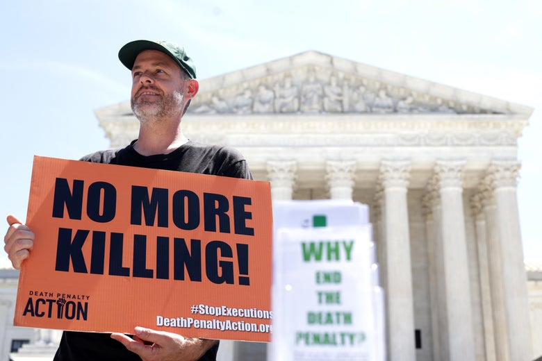 """Scott Langley of Ghent, New York, hold sign that reads """"No More Killing!"""" as he participates in a vigil against the death penalty in front of the U.S. Supreme Court on June 29, 2021 in Washington, DC."""
