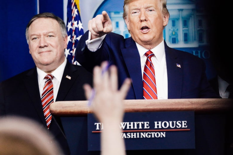 Donald Trump, standing at a lectern, stands next to Mike Pompeo and points over a raised hand.