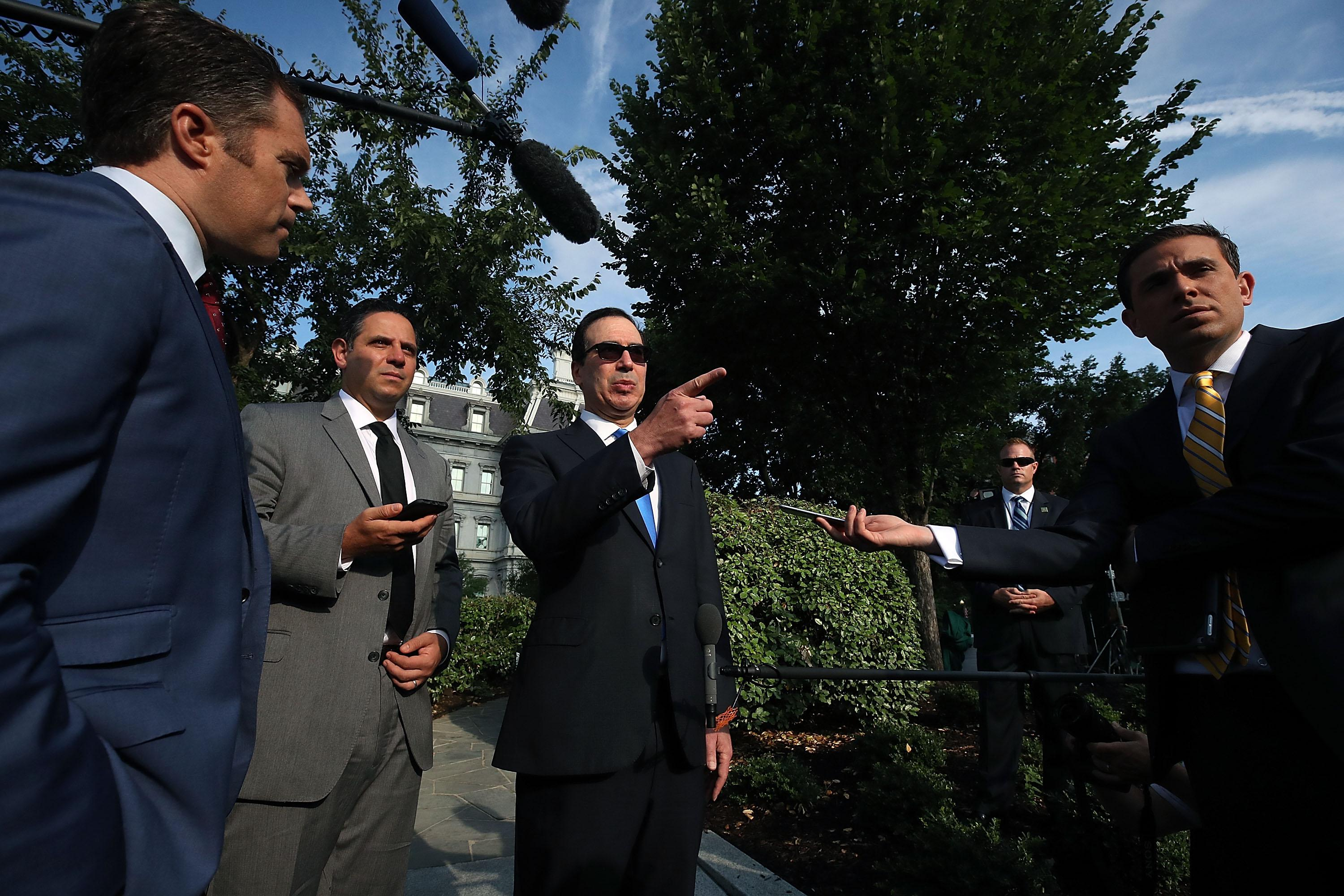 Treasury Secretary Steven Mnuchin points while talking to reporters outside the White House.