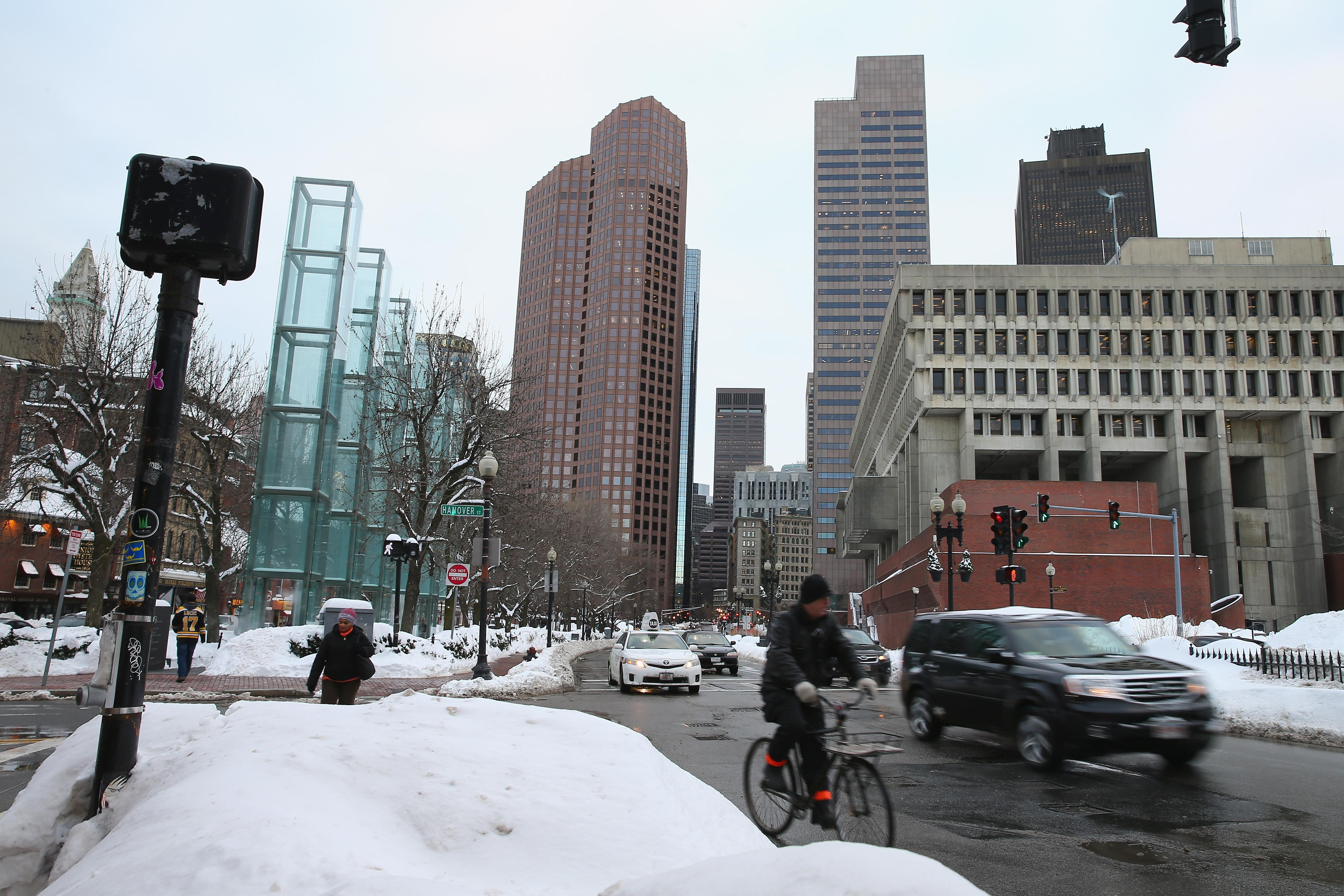 Cars and a biker at a snowy intersection in Boston.