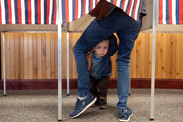 A child peeks out from between his parent's legs as the parent casts a ballot in a voting booth in a wood-paneled room