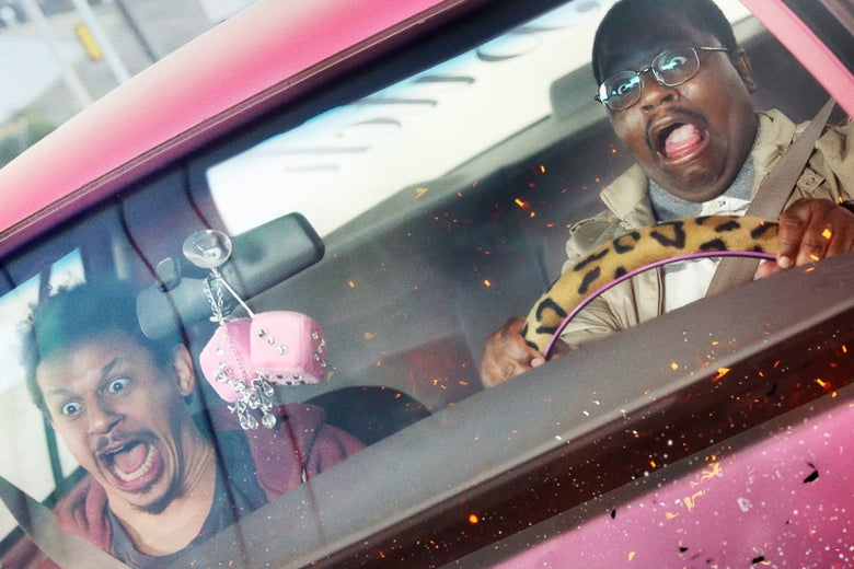 Two men sit in the front of a pink car that has pink fuzzy dice dangling from the rearview mirror and a cheetah print-covered steering wheel. They are both yelling, eyes wide, as flames begin to engulf the front of the car.