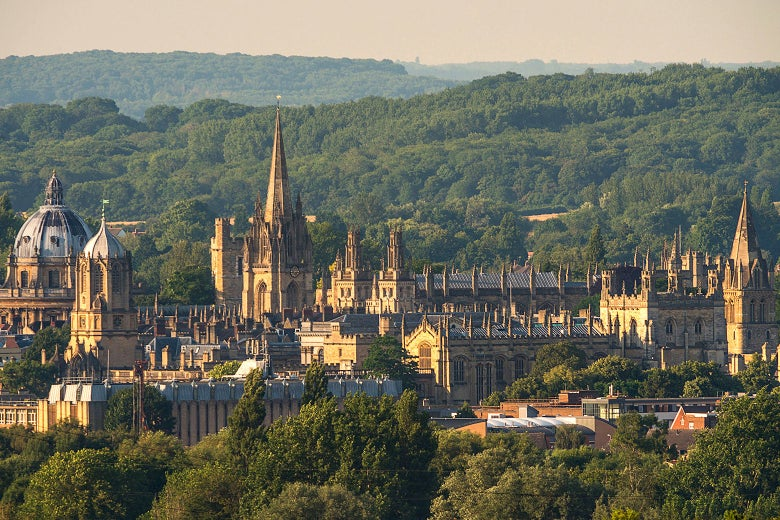 Oxford's medieval spires amid wooded hills on a sunny day.