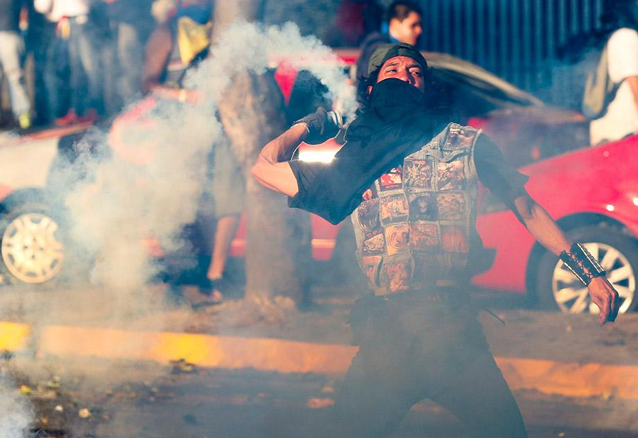 An opposition demonstrator throws a gas canister back to riot police during a protest against President Nicolas Maduro's government in Caracas.