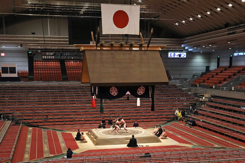 Two sumo wrestlers competing in a mostly empty arena.