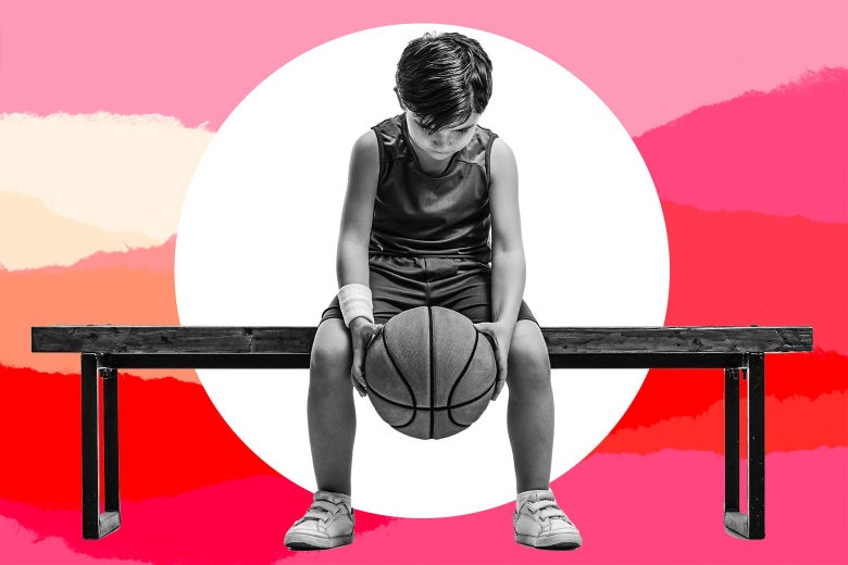 A dejected kid sits on a bench and holds a basketball.