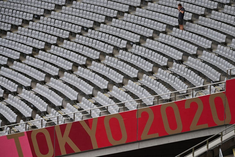 A man stands amid empty seats above a TOKYO 2020 sign.