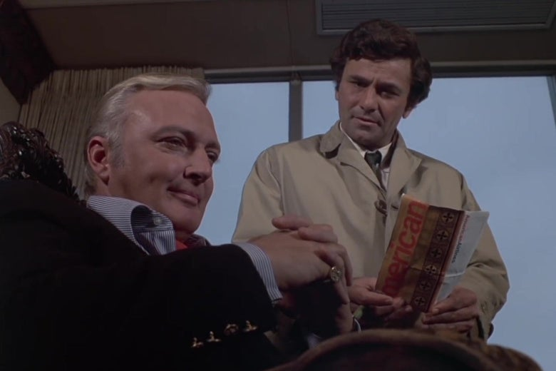 "Jack Cassidy and Peter Falk in a still from the Columbo episode ""Murder by the Book."" Cassidy sits in the foreground, smirking; Columbo stands behind him asking a question."