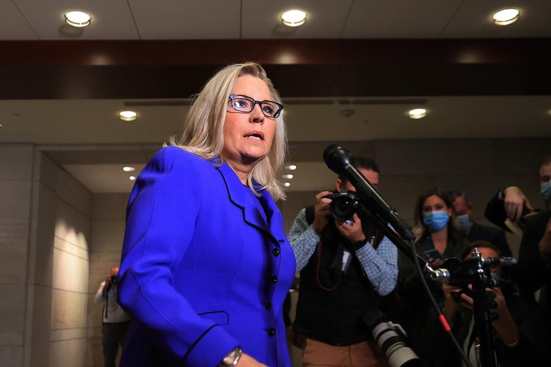 Liz Cheney speaks surrounded by press in a hallway