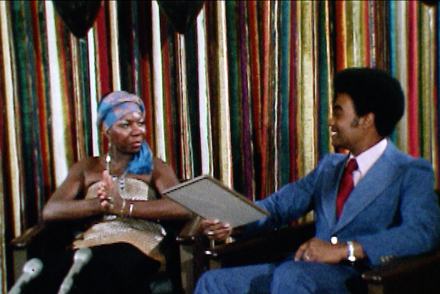 Nina Simone, in a gold lamé dress and blue headscarf, sits beside Warren Widener.