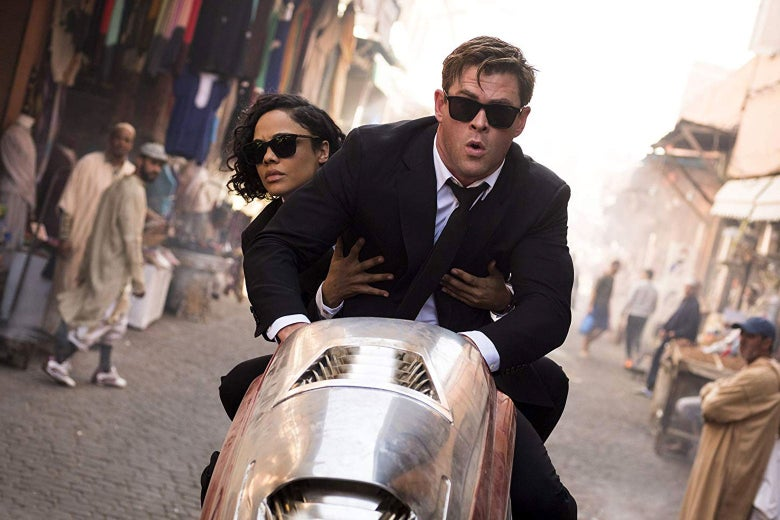 Tessa Thompson and Chris Hemsworth on a moped in a still from Men in Black: International.