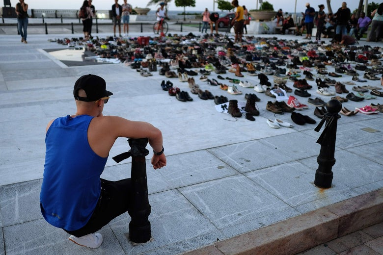 A man looks at hundreds of shoes displayed in memory of those killed by Hurricane Maria.
