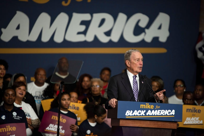"""Michael Bloomberg speaks into a podium that says """"Mike for Black America,"""" as black supporters sit behind him."""