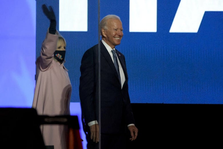Biden smiles in front of a large blue screen as his wife Jill, standing beside him, waves.