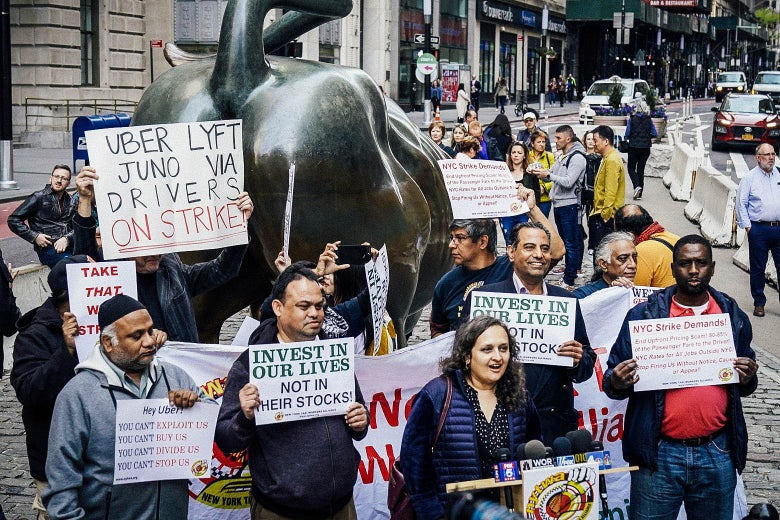 "Next to the Charging Bull, protesters hold signs with slogans such as ""INVEST IN OUR LIVES NOT IN THEIR STOCKS,"" ""UBER LYFT JUNO VIA DRIVERS ON STRIKE,"" and ""YOU CAN'T EXPLOIT US."""