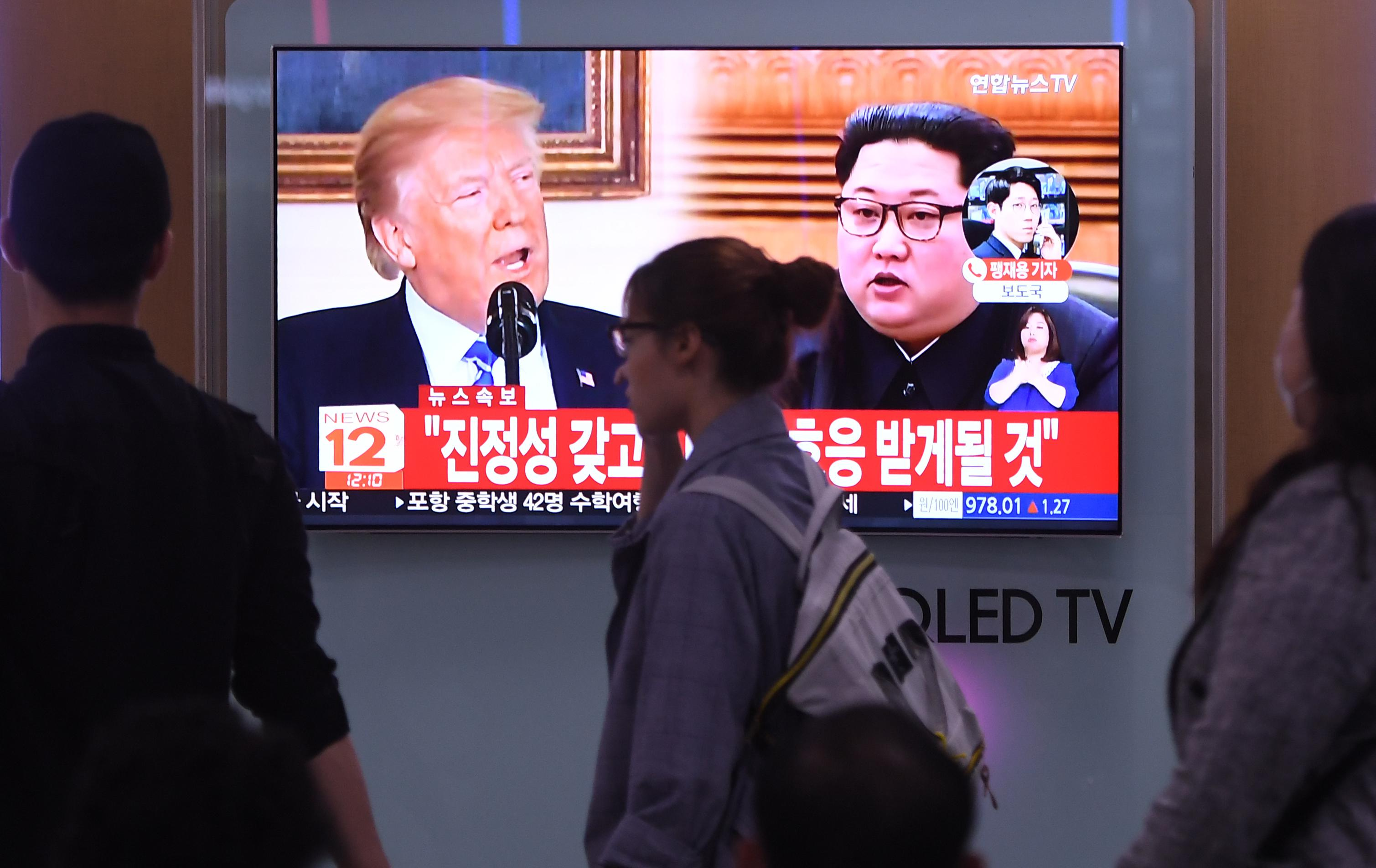 People walk past a television news screen showing North Korean leader Kim Jong Un (R) and US President Donald Trump (L) at a railway station in Seoul on May 16, 2018. - North Korea threatened on May 16, to cancel the forthcoming summit between leader Kim Jong Un and President Donald Trump if Washington seeks to push Pyongyang into unilaterally giving up its nuclear arsenal. (Photo by Jung Yeon-je / AFP)        (Photo credit should read JUNG YEON-JE/AFP/Getty Images)