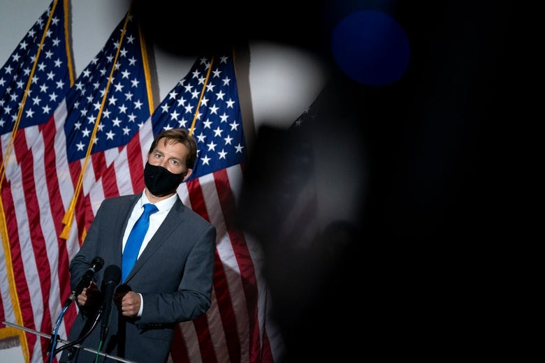 Sasse is seen on the left side of the image wearing a black mask standing between a microphone stand and three American flags. The right side of the image is occluded by an unidentifiable object near the camera lens.