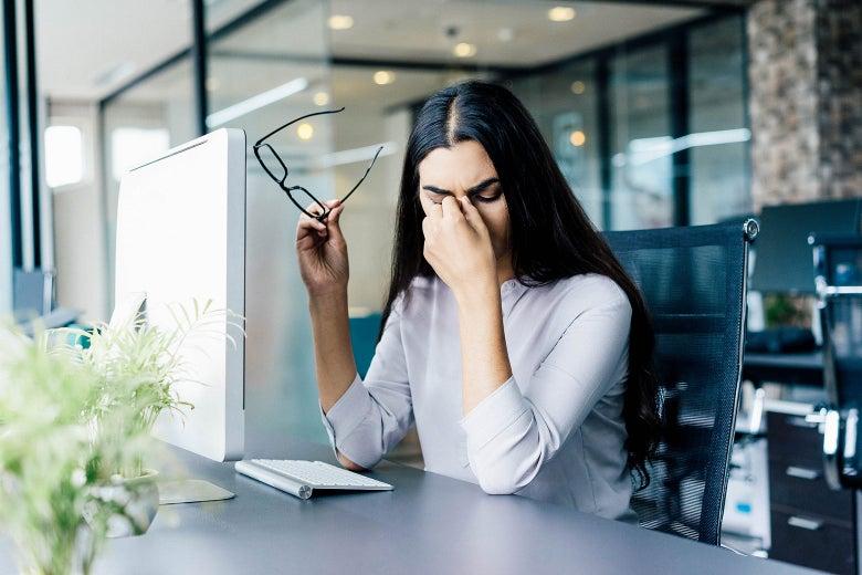 Businesswoman at her desk, rubbing her eyes.