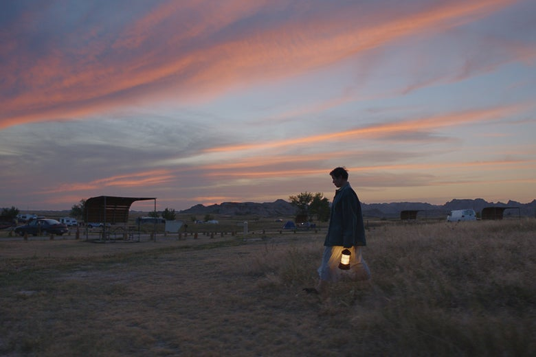 She walks through the brush near a rural parking lot against a colorful sky, carrying a lantern.