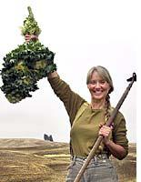 Me, holding up kale, with my farm behind me