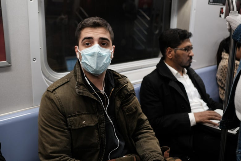 A man wearing a face mask on the subway.