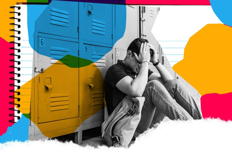 A teenager sits against a row of lockers with his head in his hands.