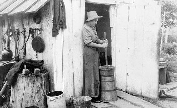 A woman churns butter in 1893.