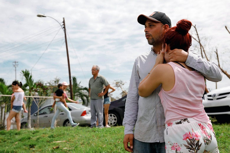 Local residents react while they look at the water flowing over the road at the dam of the Guajataca Lake on Saturday after Puerto Rico was hit by Hurricane Maria.