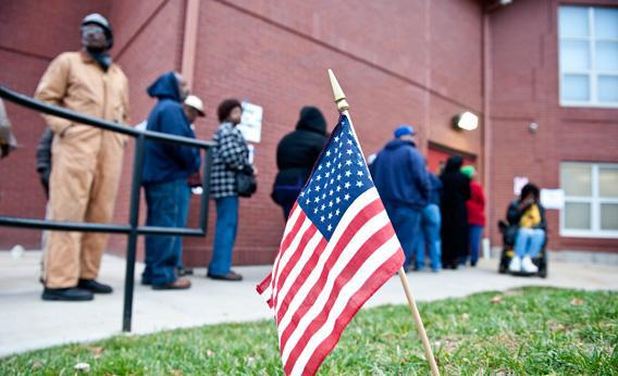 An American flag flutters in the grass as voters wait in line to cast their vote.
