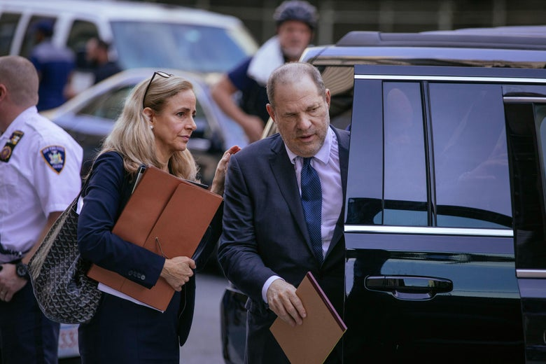 Harvey Weinstein entering a large black vehicle. A woman holding a folder touches his shoulder.
