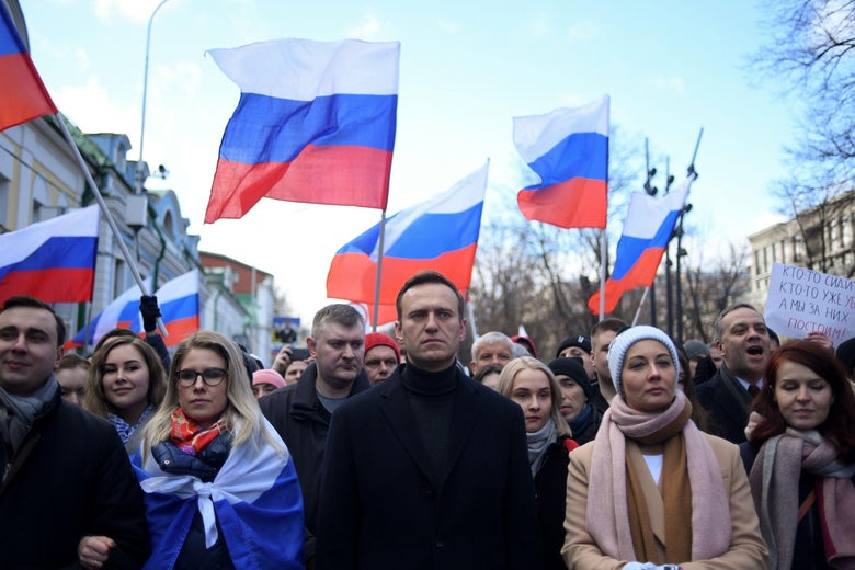 Aleksei Navalny is seen in a crowd of people holding Russia flags aloft.