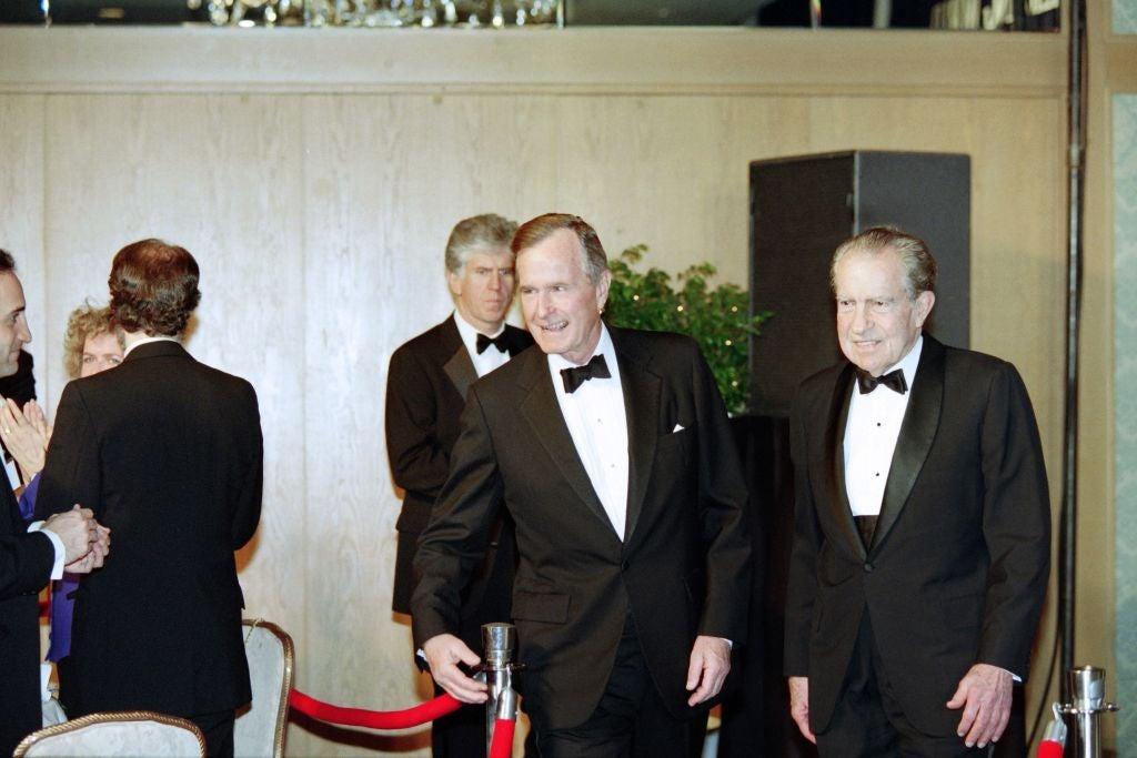 Bush and Nixon smiling while wearing tuxedoes.