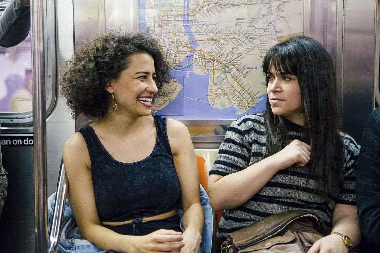 Ilana Glazer and Abbi Jacobson sitting in a New York City subway car, in a scene from Broad City.