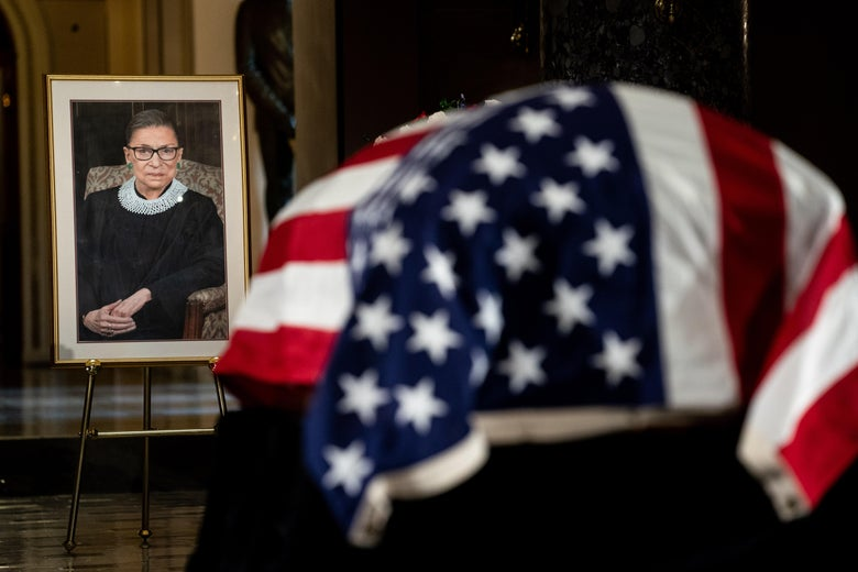 The flag-draped casket of RBG is seen near a framed portrait of her.