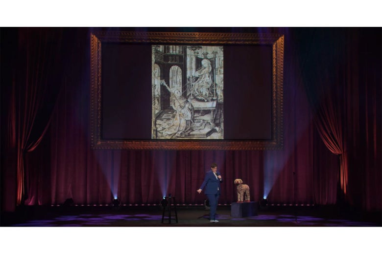Hannah Gadsby stands on stage in front of a projection of an engraving of St. Bernard kneeling while Mary lactates into his mouth.