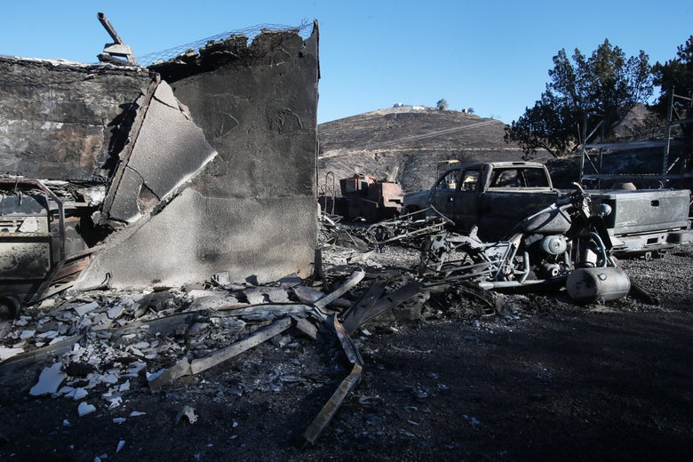 A structure and vehicle stand scorched by the Tick Fire on Friday in Canyon Country, California.