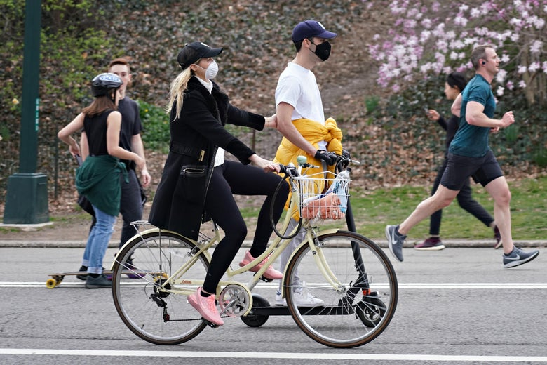 A couple riding a bike and scooter wearing protective masks in Central Park as the coronavirus continues to spread across the United States on March 20, 2020 in New York City.