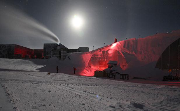 South Pole employees remove snow from the top of buildings during the winter darkness, on May 9, 2012.