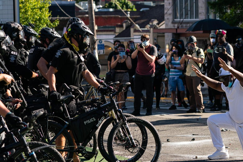 A demonstrator kneels in front of police during protests on July 25, 2020 in Seattle, Washington.