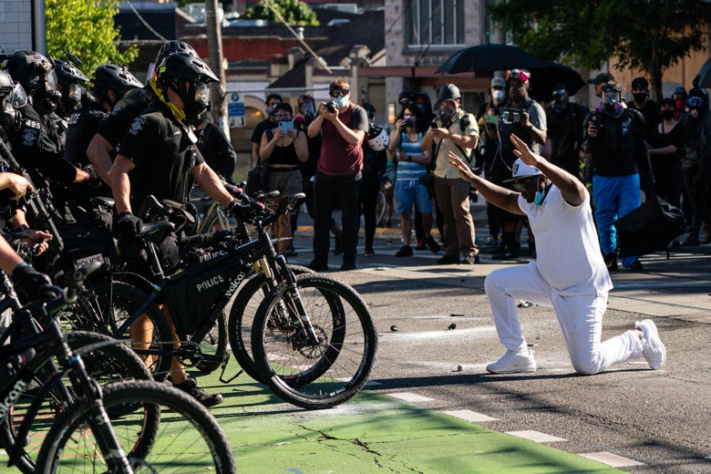 A demonstrator kneels in front of police who are standing with bikes.