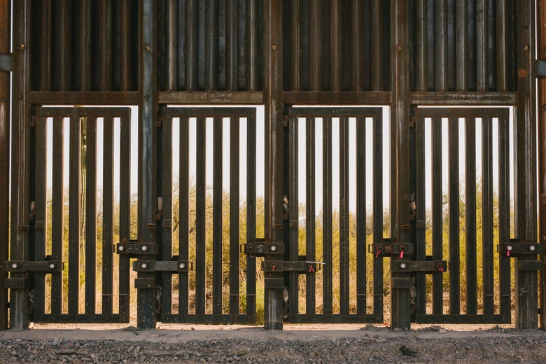 """""""Doors"""" with open metal slats at the bottom of a fence."""
