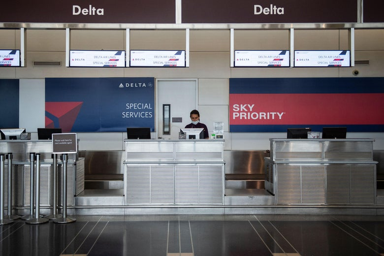 A Delta Air Lines employee waits for passengers at an empty check-in counter in Ronald Reagan Washington National Airport in Arlington, Virginia, on May 12, 2020. - The airline industry has been hit hard by the COVID-19 pandemic, with the number of people flying having decreased by more than 90 percent since the beginning of March. (Photo by ANDREW CABALLERO-REYNOLDS / AFP) (Photo by ANDREW CABALLERO-REYNOLDS/AFP via Getty Images)
