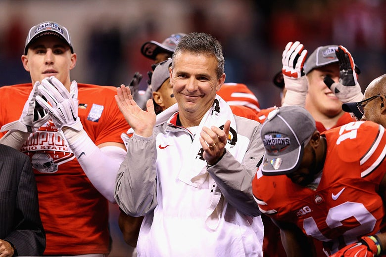 Meyer, surrounded by players, claps with a smug expression on his face.
