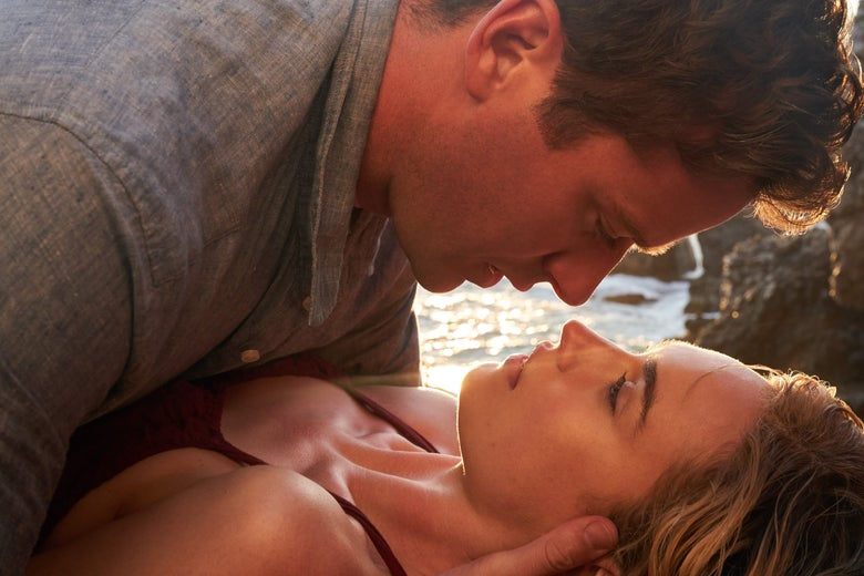 Armie Hammer lies on top of Lily James, looking into each others' eyes. Sunlight glints off the water behind them.