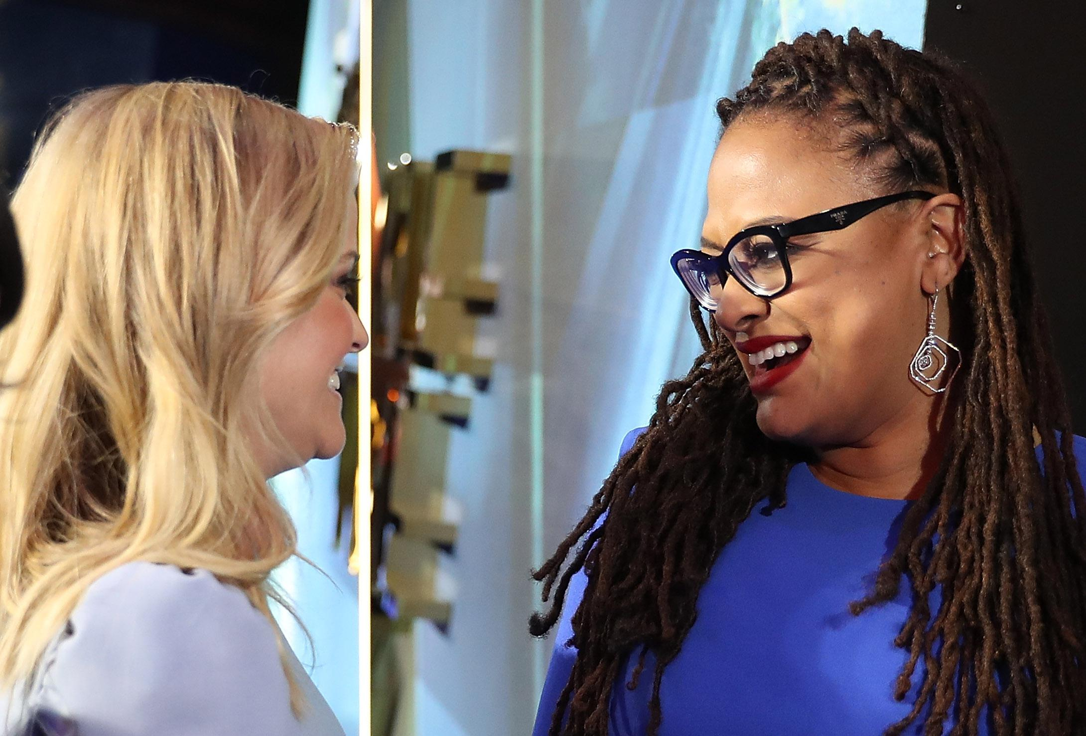 Reese Witherspoon and Ava Duvernay face each other, smiling, on the Wrinkle in Time red carpet.