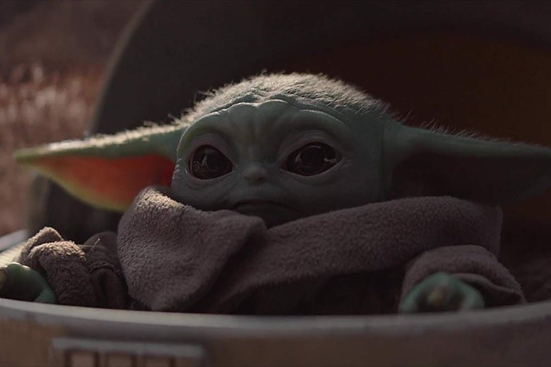 The adorable Baby Yoda creature from the Mandalorian, poking its head up from its pram.